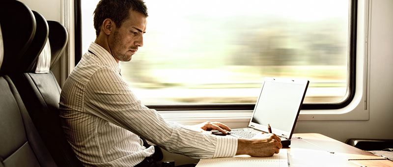man using laptop on train