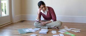 woman looking at tax files spread on floor